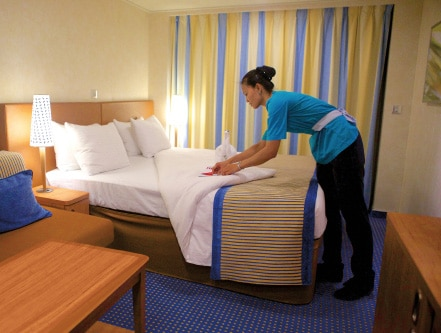 Carnival staff member cleaning and folding bed sheets.