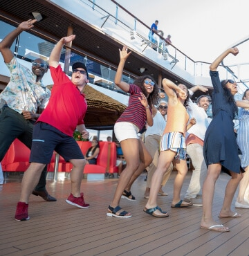 Carnival staff and cruise-goers dancing on the deck enjoying themselves.