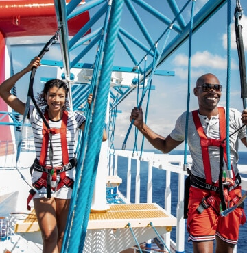 Young couple on Carnival cruise ship hanging out on the SkyCourse activity.