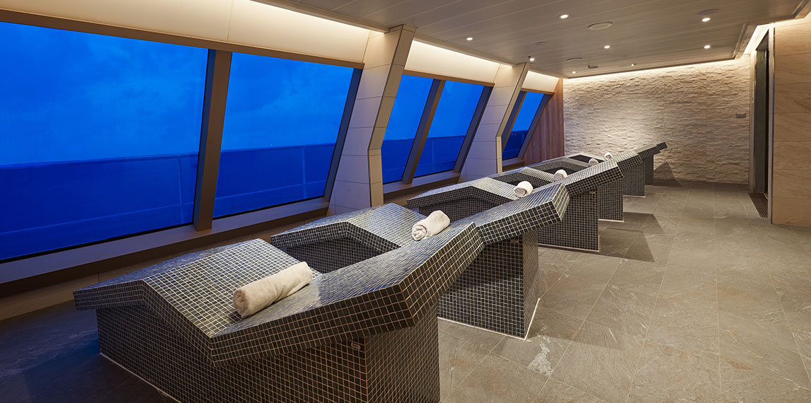 Interior of relaxation beds with ocean view out of window.
