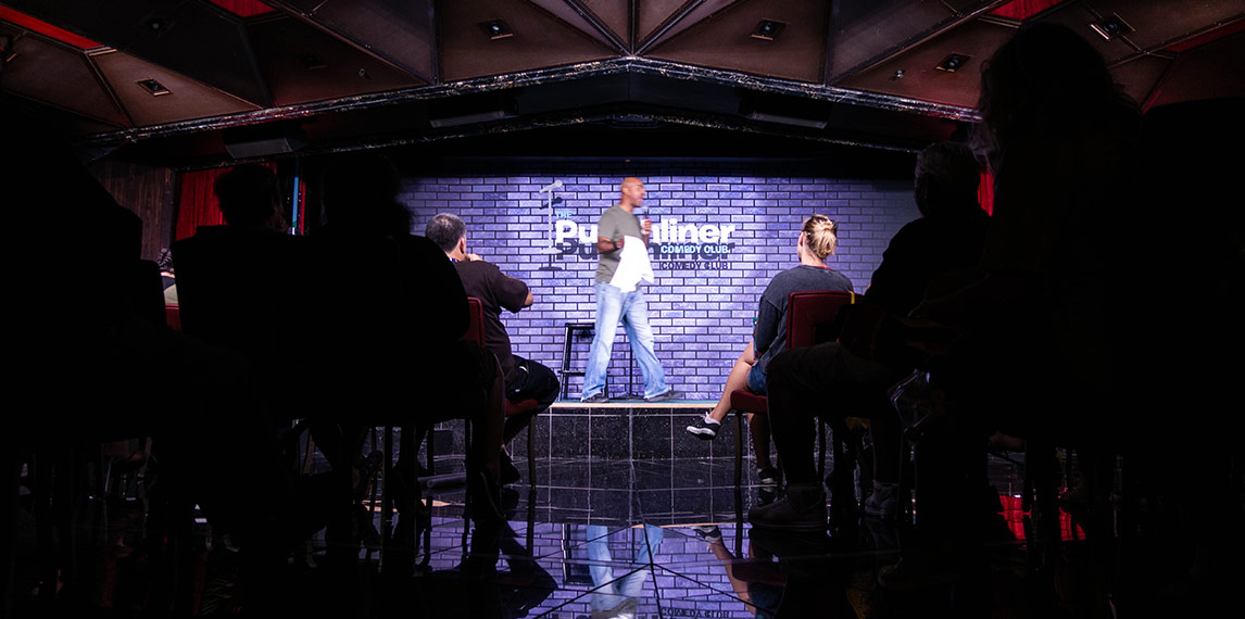 Comedian on stage performing at Punchliner comedy club.