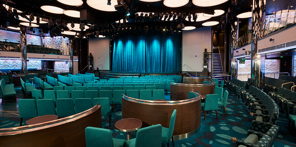 Mid size auditorium that has a large stage with booth style seating.
